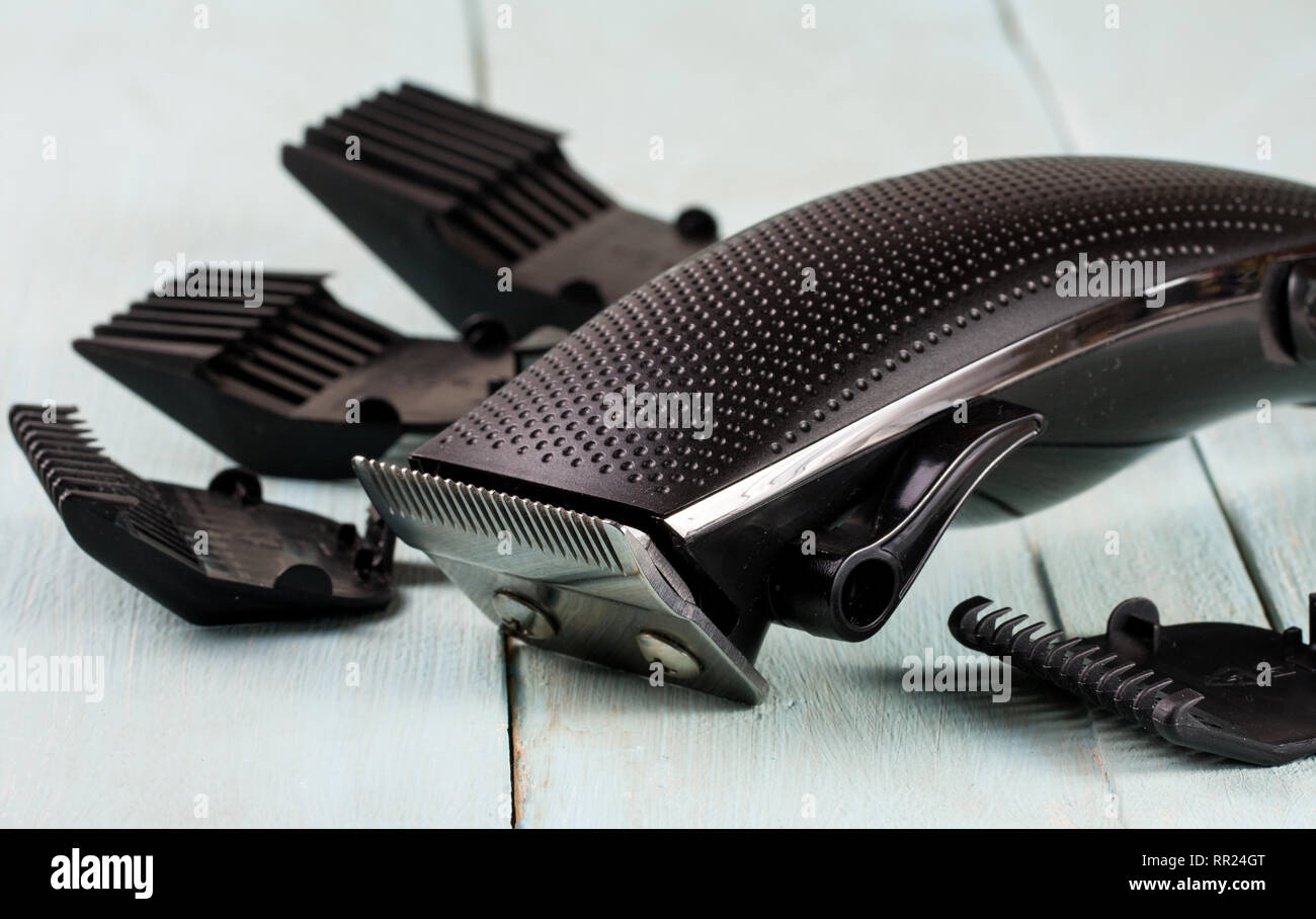 hair trimmer with attachment on a light wooden background closeup - Stock Image