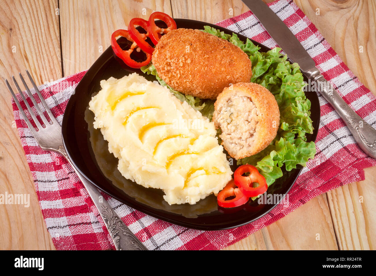 two fried breaded cutlet with mashed potatoes and lettuce on a black plate wooden background - Stock Image