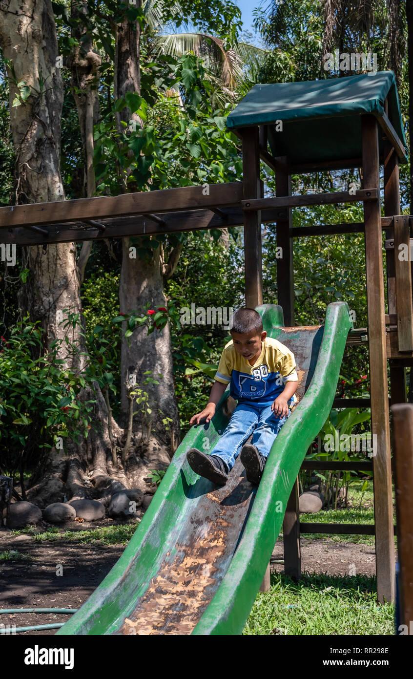 young latin boy playing on slide in Guatemalan playground Stock Photo