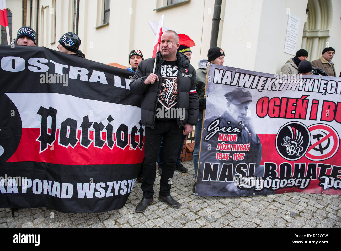 """A man see standing next to banners during commemorative. Polish nationalists organized a commemorative march of the """"Cursed Soldiers"""" in the city of Hajnowka next to the Belarusian border. The Cursed Soldiers also known as the Doomed Soldiers were anti-communist resistant fighters after WWII, however they were also famous of committing crimes against civilians, mostly ethnic Belarusians. - Stock Image"""