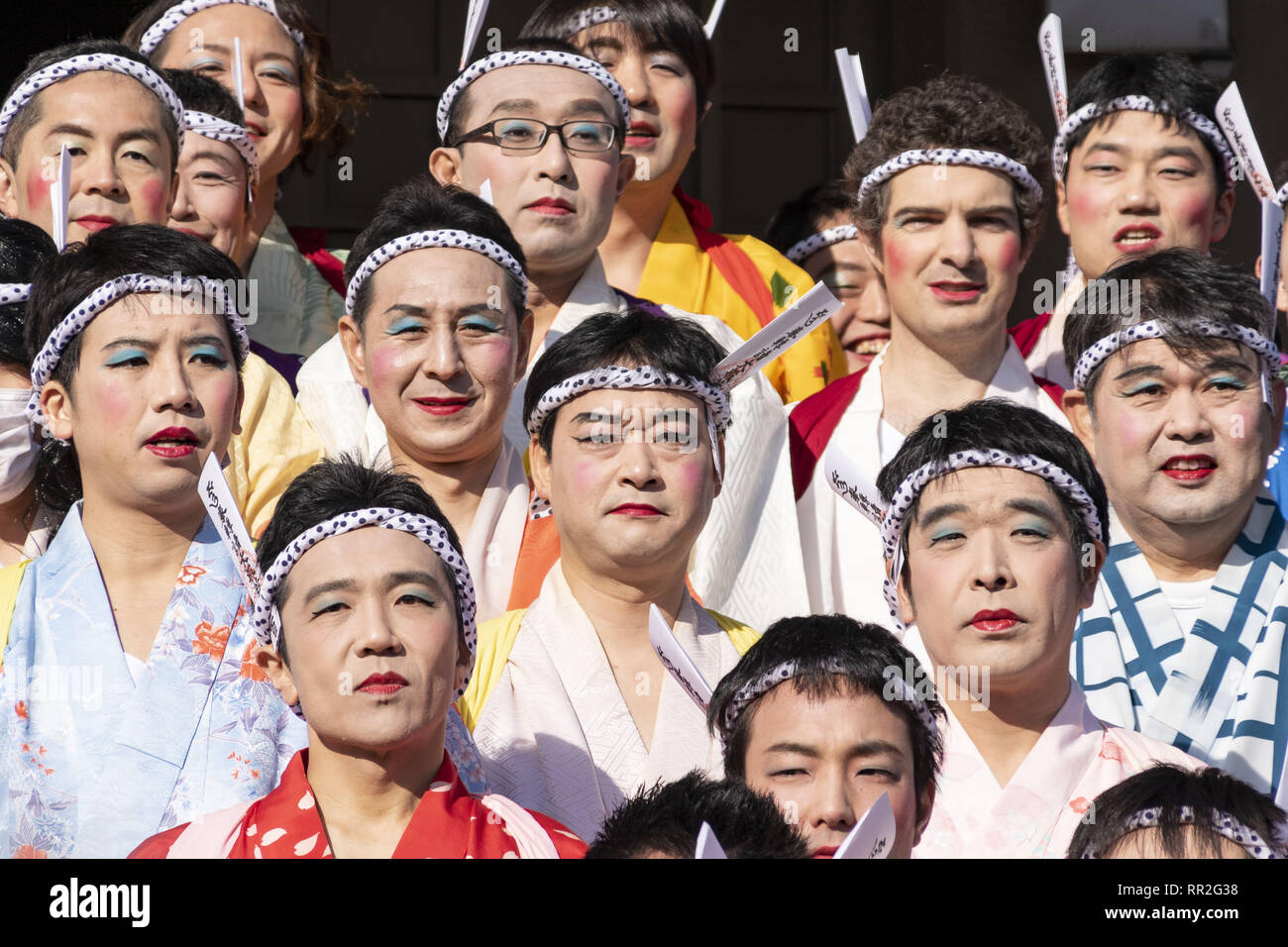 Tokyo, Japan. 24th Feb, 2019. Participants dressed in women's kimonos and wearing makeup, pose for a group photo during the Ikazuchi no Daihannya festival in the Shinzoin Temple. Festival volunteers carry 6 containers from the Shinzoin Temple around the neighborhood to chase away evil spirits. The origins of this annual event are disputed, but the legend tells the priest of Shinzoin Temple visited house to house to prevent the spread of cholera during the late Edo era. Another legend of a man who lived in the neighborhood dressed in women's kimono to scare away the bad spirits for his si Stock Photo