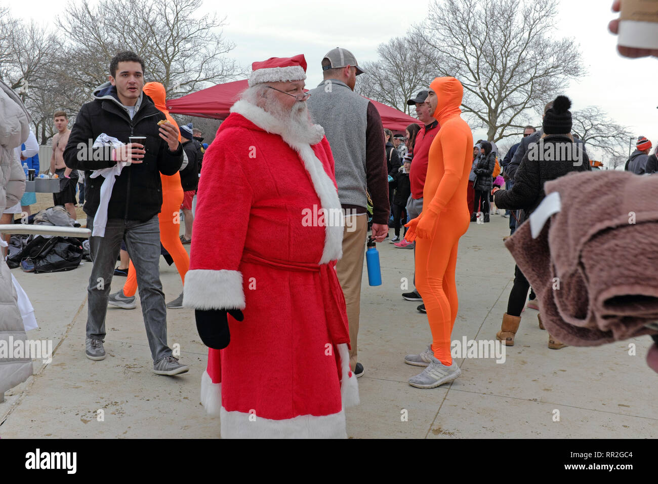 Cleveland, Ohio, USA.  24th Feb, 2019.  Santa makes his way through the crowd of fellow Polar Plunge participants at Edgewater Park in Cleveland, Ohio, USA.  Over 400 participants braved the elements by taking a dip in the ice-laden shore waters of Lake Erie.  The fun annual event encourages people to dress in costumes as they raise money for the Special Olympics.  Credit: Mark Kanning/Alamy Live News. - Stock Image