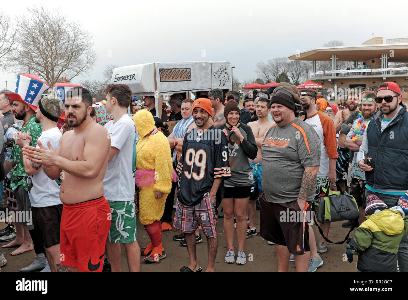 Cleveland, Ohio, USA.  23rd Feb, 2019.  Participants in the 2019 Cleveland Polar Plunge to benefit the Special Olympics brave the winter cold air before taking the plunge into the ice-filled waters of Lake Erie.  This annual event draws participants and spectators to the Cleveland Metroparks Edgewater Park on the shores of Lake Erie for a fun-filled wintertime event.  Credit: Mark Kanning/Alamy Live News. - Stock Image