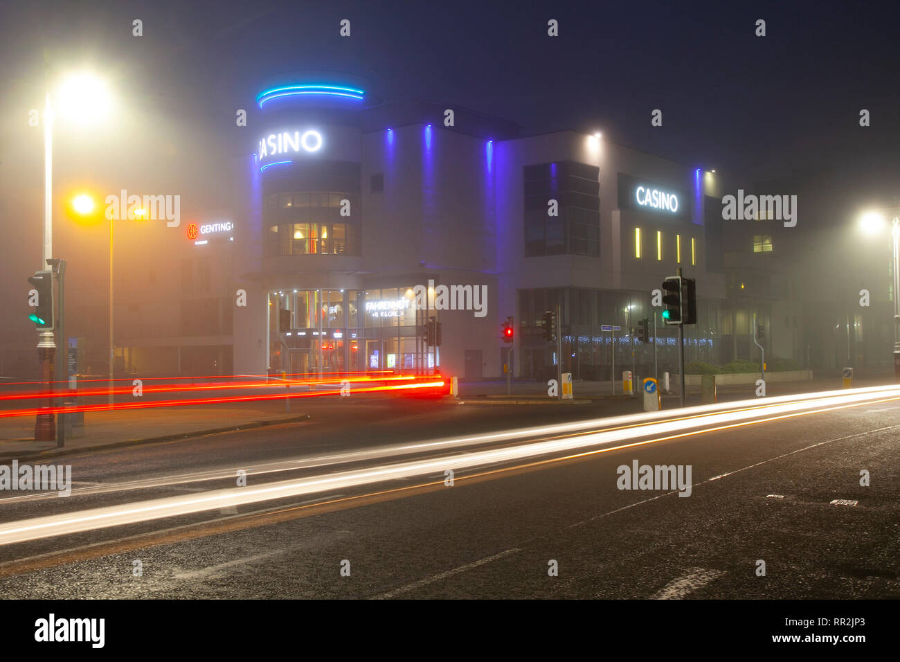 Southport, Merseyside. 24th February, 2019. UK Weather. Hazy, foggy, misty start to the day with light drizzle as early morning city centre traffic lights up the damp pavements. Traffic trails from late night revellers using homebound taxis; as lights from passing vehicles leave reflections on the road surface. Credit: MWI/AlamyLiveNews. - Stock Image
