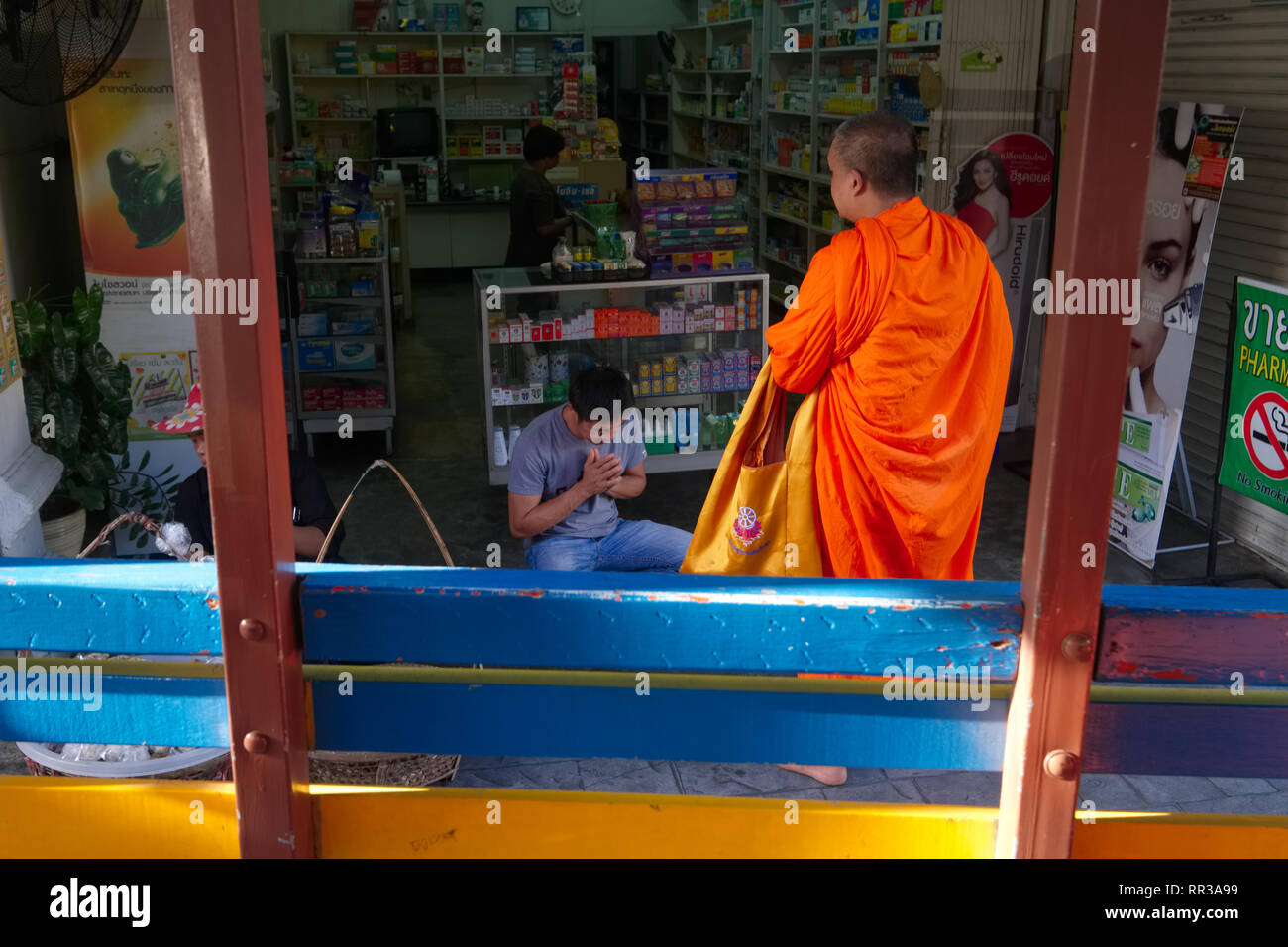 A worshipper kneels in front of a Buddhist monk in Phuket Town, Phuket, Thailand, seen from inside a songthaew, a traditional, basic kind of local bus - Stock Image