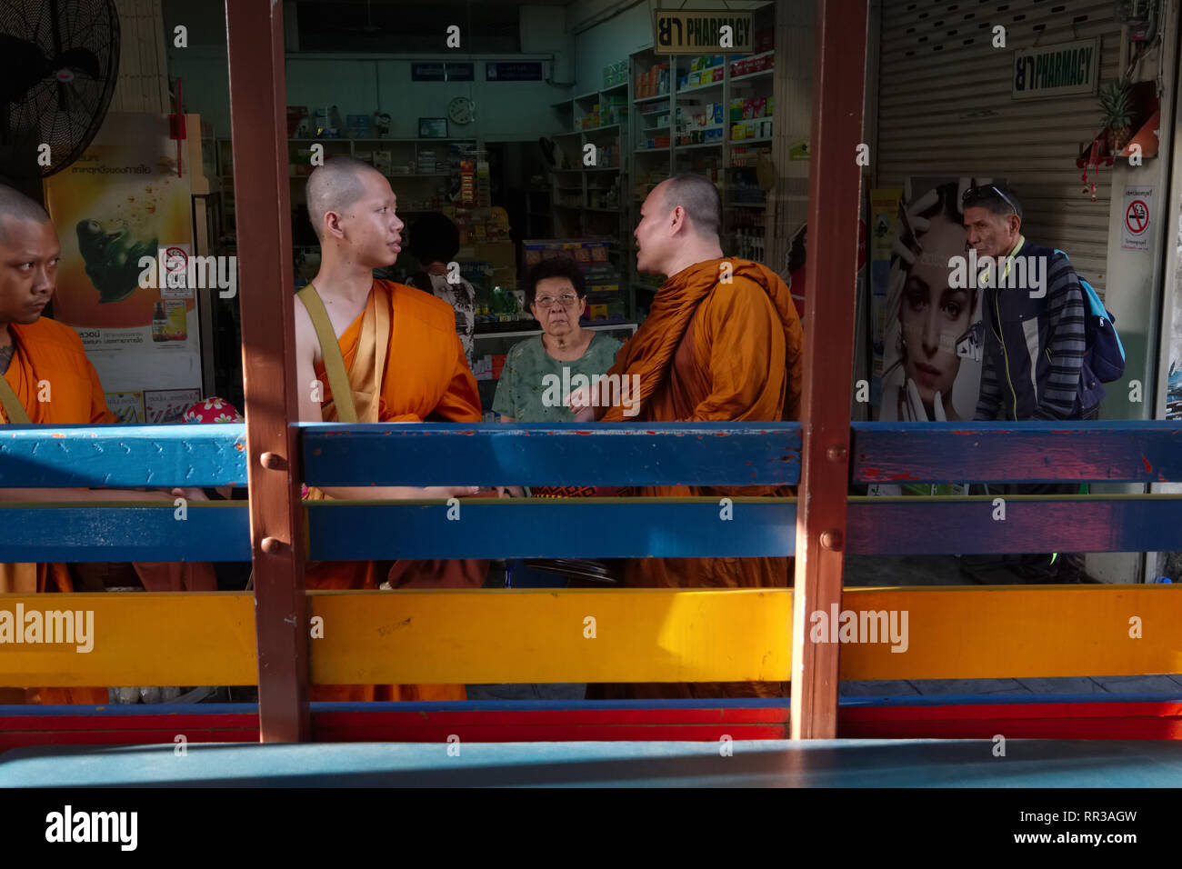 Buddhist monks waiting at a bus stop in Phuket Town, Phuket, Thailand, seen from inside a songthaew, a traditional, basic kind of local bus - Stock Image