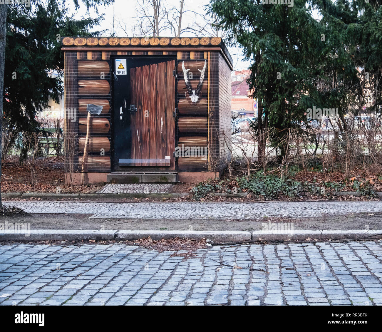 Heidelberger Platz, Wilmersdorf-Berlin.Utility box disguised as forester's shed - Paintwork of logs, ax and deer antlters Stock Photo