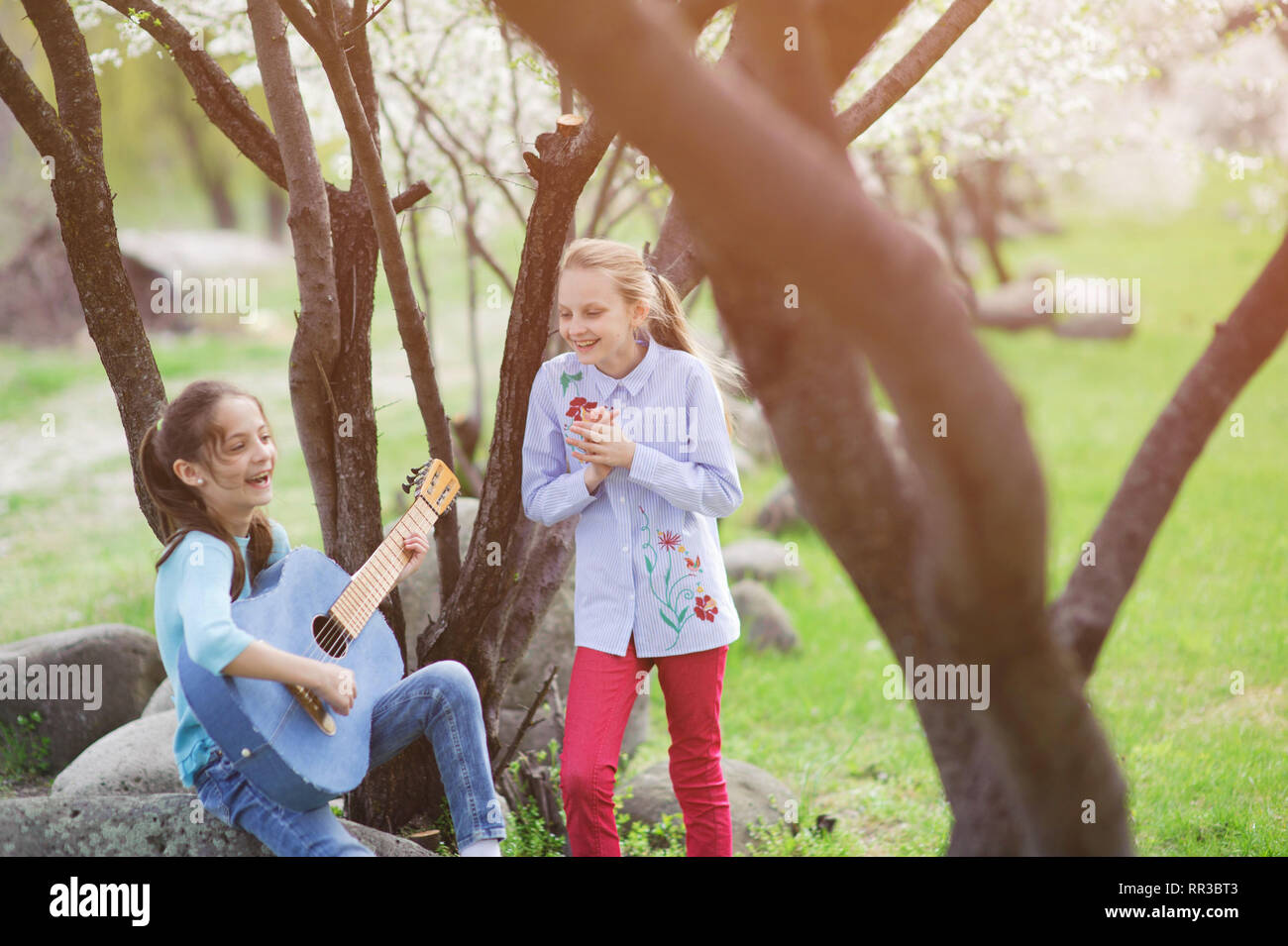 two happy caucasian laughing little girls playing guitar and applauding in spring outdoor park - Stock Image