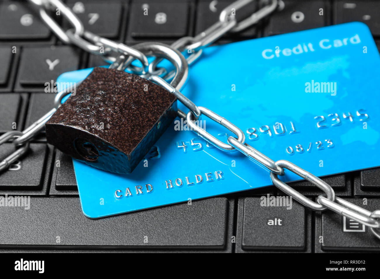 Credit card in chain with lock on laptop keyboard. Ban online payments and purchases in the online store. Stock Photo