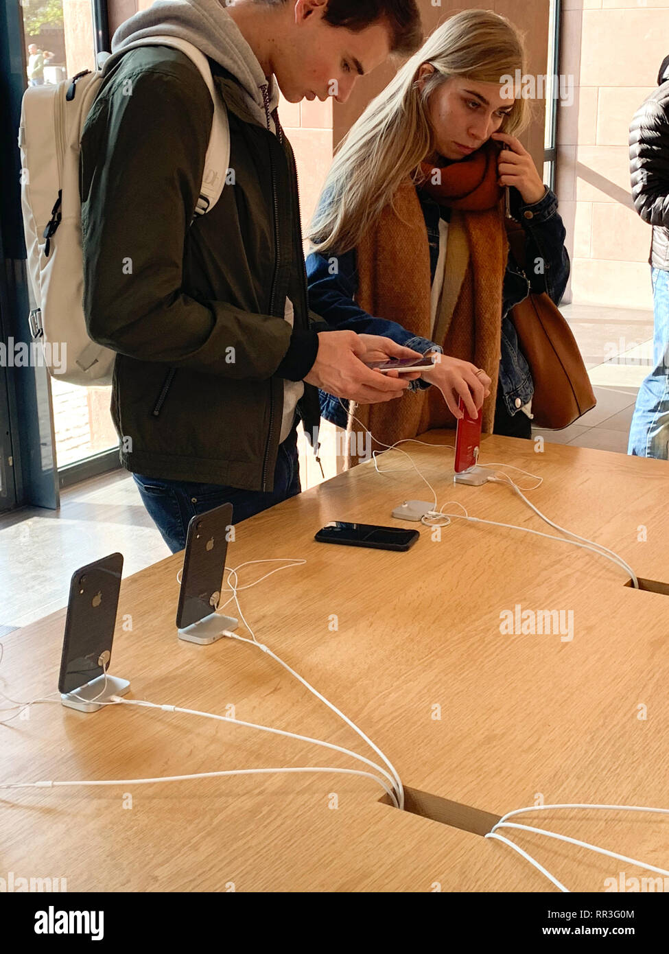 PARIS, FRANCE - OCT 26, 2018: Side view of young couple admiring the latest iPhone XR smartphone in Apple Store Computers during the launch day - Stock Image