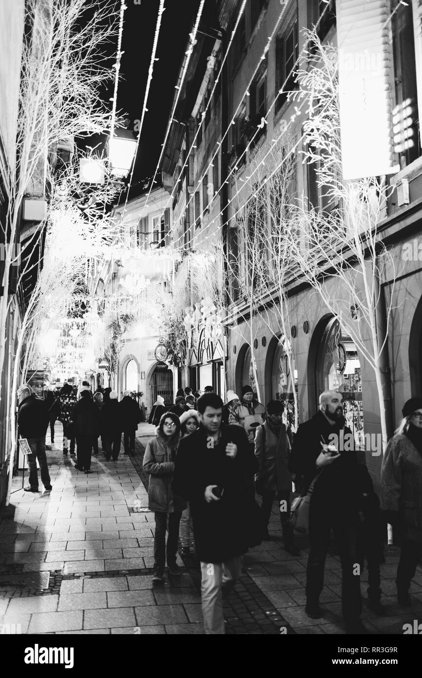STRASBOURG, FRANCE - NOV 29, 2017: Pedestrians walking late in the evening under the illuminated garlands  and Christmas Market decorations on the iconic Rue des Orfevres in Strasbourg - black and white - Stock Image