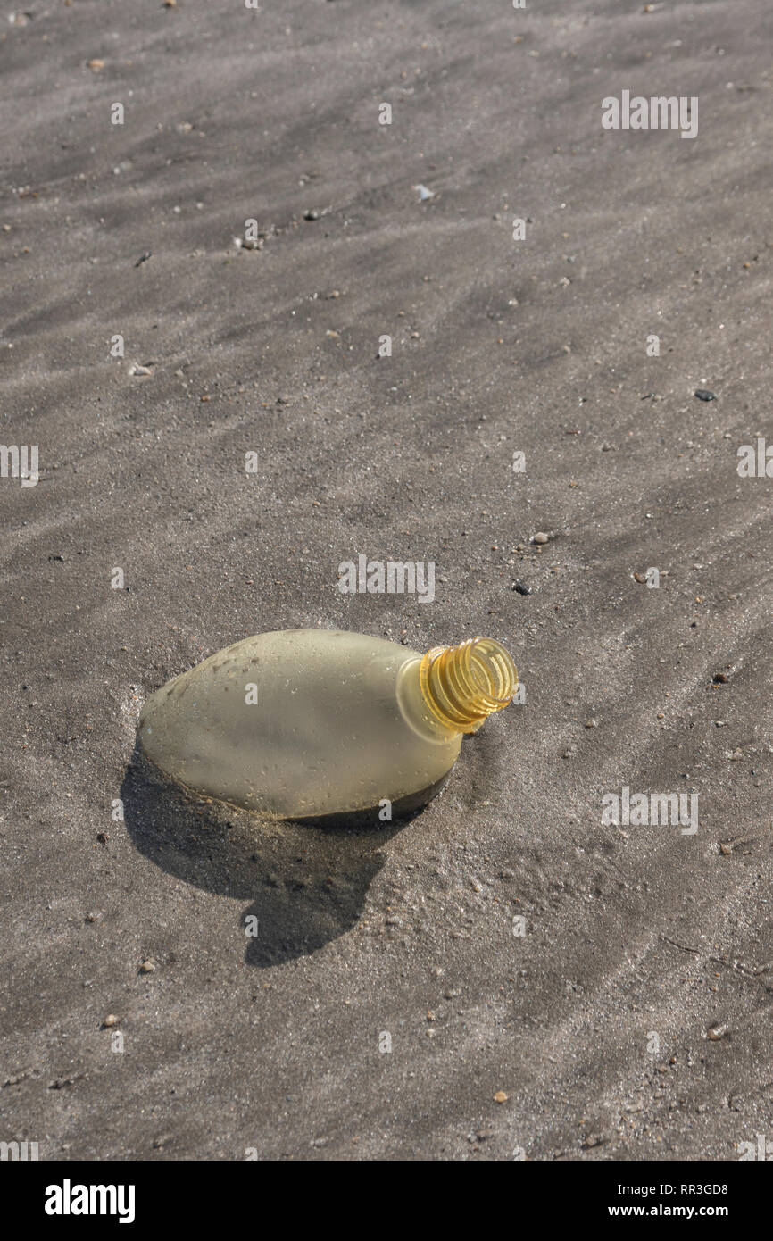 Empty discarded plastic soft drink bottle left embedded in silty sand of a beach. Metaphor plastic pollution, ocean polluting plastic. - Stock Image