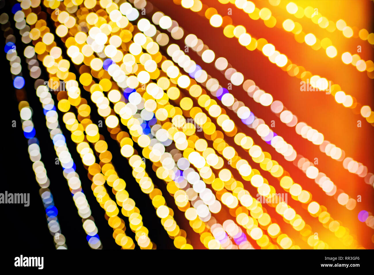 Abstract defocused bokeh illuminated garland view from below in central city square decoration for the annual Christmas Market - Strasbourg, Alsace, France - yellow and blue led lights Stock Photo