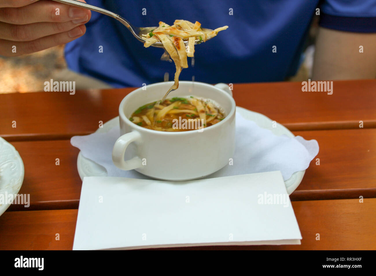 Closeup young man eating hot soup in beer garden or restaurant - Stock Image