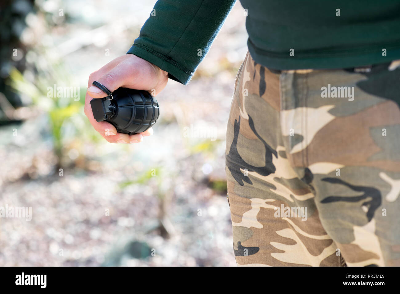 Close up on the hand of a man holding a grenade outdoors in a concept of terrorism or combat - Stock Image