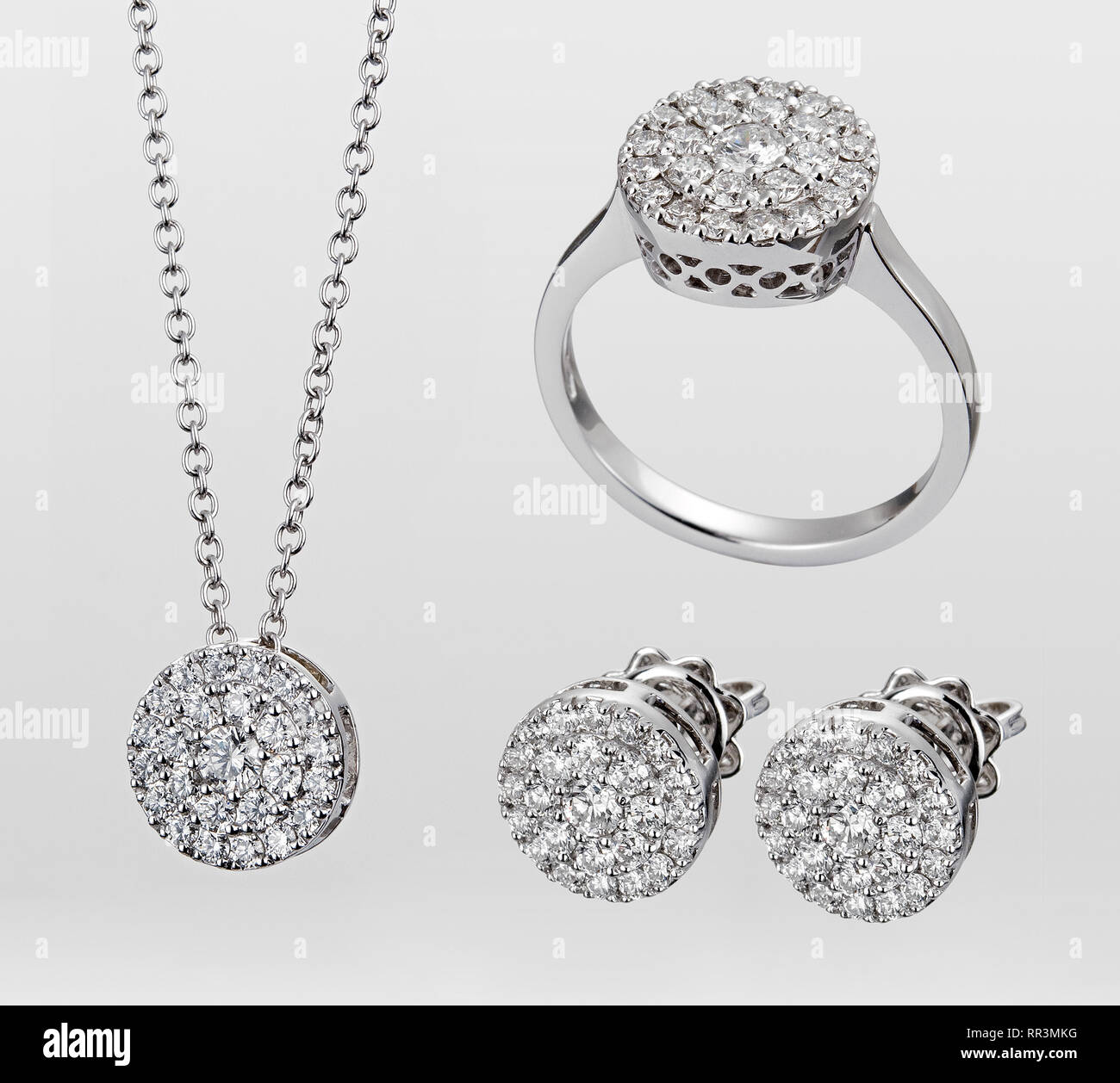A demi-parure of gemstone jewellery in white gold or silver consisting of three matching pieces - necklace, earrings and ring isolated over a white ba - Stock Image