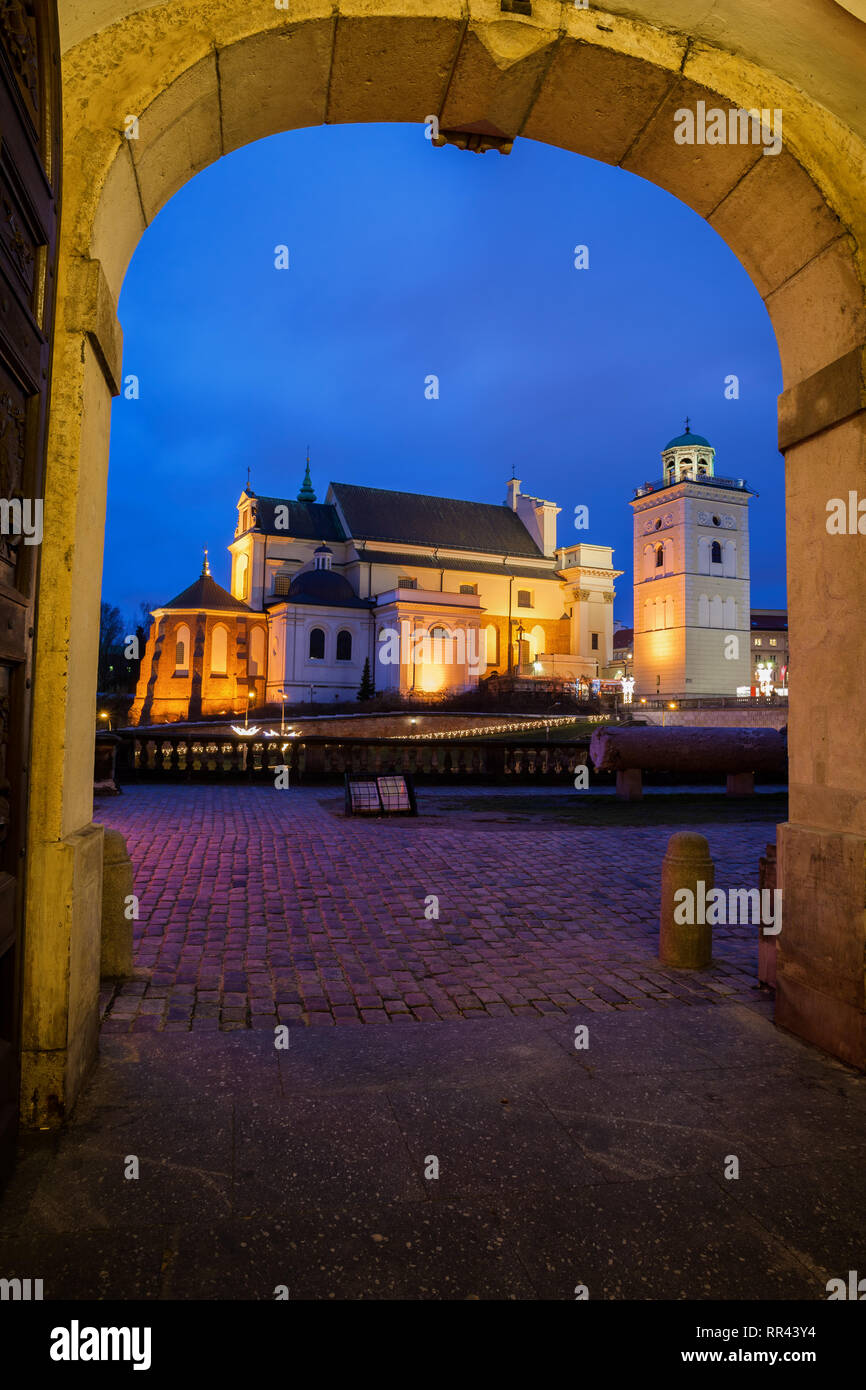 View to St. Anne's Church at night from arched gate of the Royal Castle in city of Warsaw in Poland Stock Photo