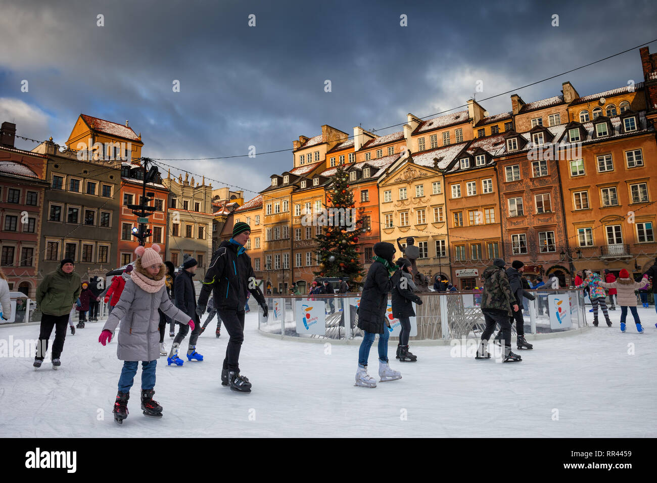 Poland, city of Warsaw, people skating on ice rink at Old Town Market Sqaure at sunset, historic tenement houses in the background, Christmas time. - Stock Image