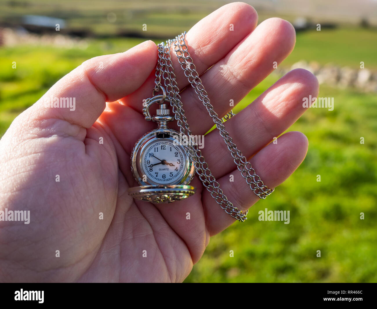 One person with one antique chain watch plated in his hand - Stock Image