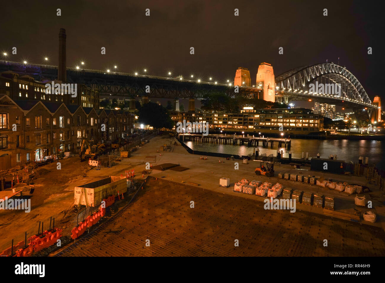 Sydney Harbour Bridge at night. The harbour front is undergoing renovation. - Stock Image