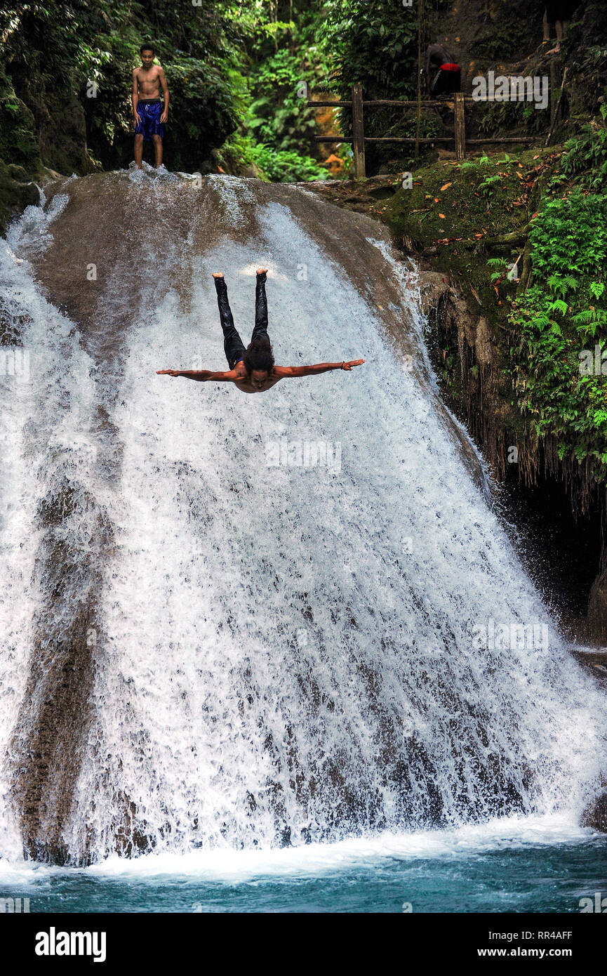 A man dives off Blue hole waterfall at Island Gully Falls near Ocho Rios on the Caribbean island of Jamaica. - Stock Image