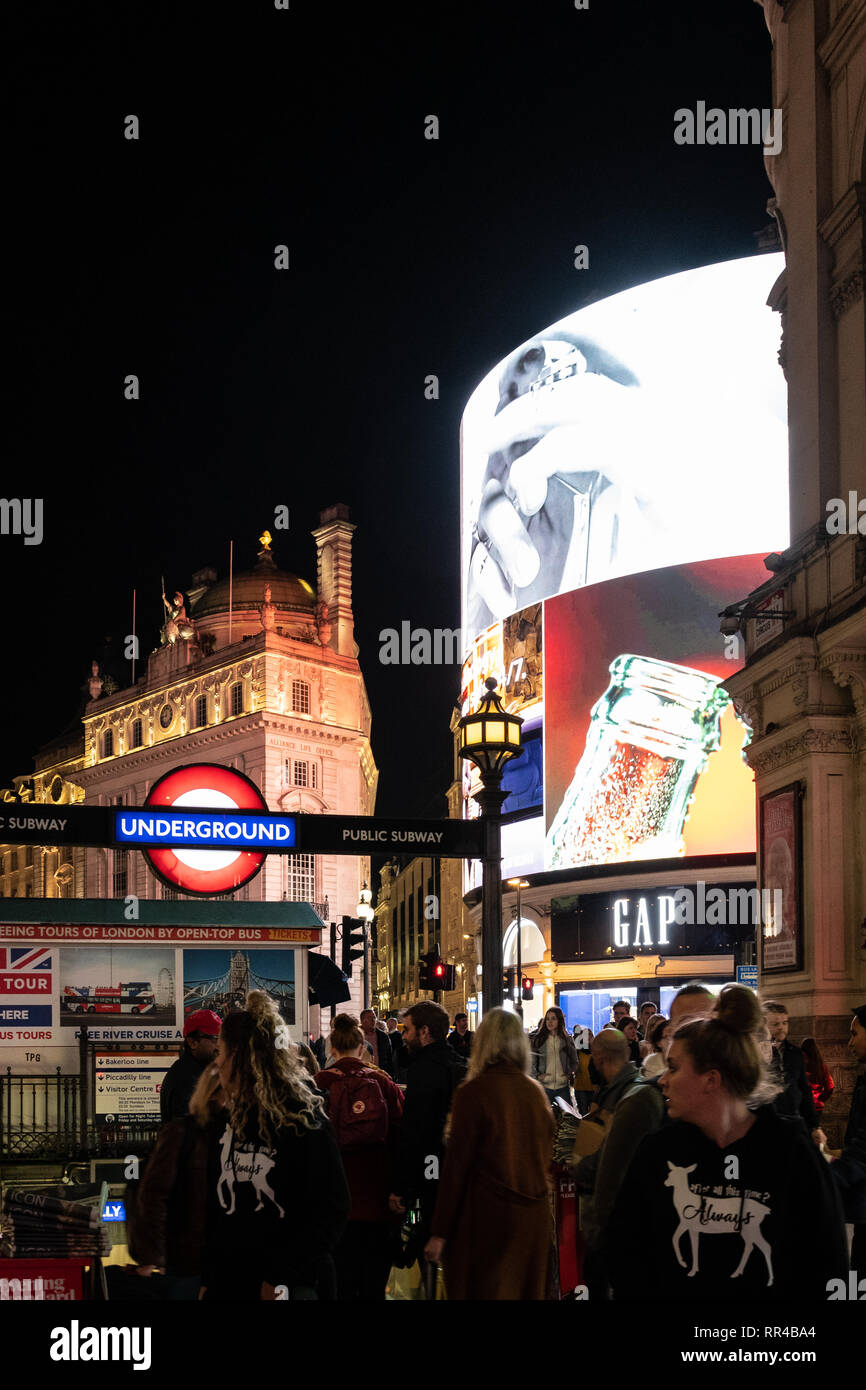 London, United Kingdom - October 18 2018:   Night shot of crowds entering and exiting the underground station at Picadilly Circus - Stock Image