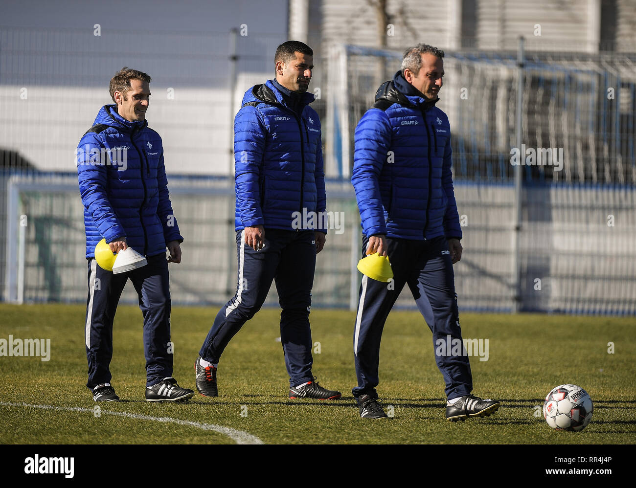 Darmstadt, Germany. 24th Feb, 2019. The new lily trainer team with Sven Thur (l-r), assistant trainer, Dimitrios Grammozis, head coach, and Iraklis Metaxas, assistant trainer, cross the field. Darmstadt 98 officially introduces its new head coach. Credit: Andreas Arnold/dpa/Alamy Live News - Stock Image
