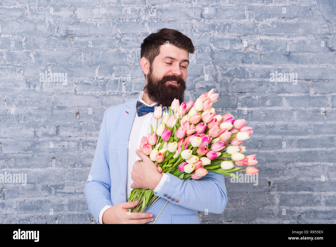 Romantic man with flowers. Romantic gift. Macho getting ready romantic date. Tulips for her. Man well groomed tuxedo bow tie hold flowers bouquet. From sincere heart. Things that make man gentleman. - Stock Image