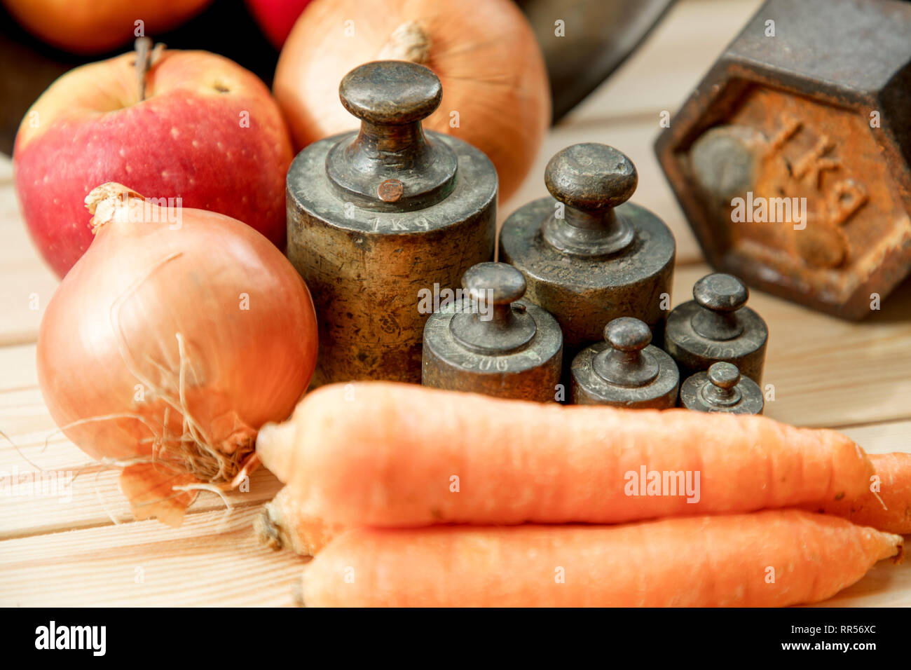 Old rusty scale weight on wooden table, Old rusty iron scale weight, vegetables - Stock Image
