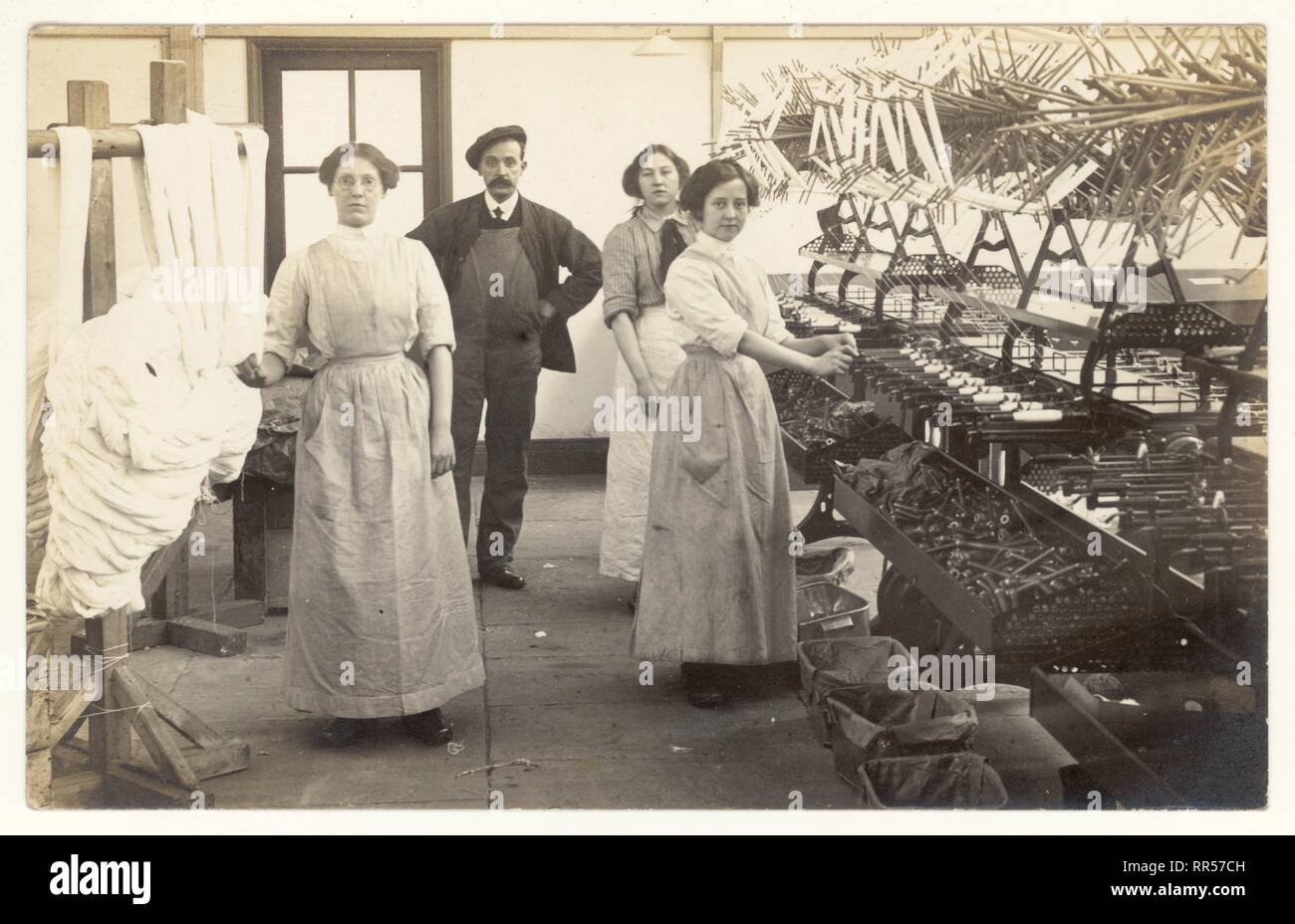 Early 1900's postcard of bobbin winder girls and foreman, overseer or workman. Dried skeins of cotton from the rack are put on the swift of the winding machine that winds yarn from the skein onto bobbins, Circa 1915, Lancashire, U.K. Stock Photo
