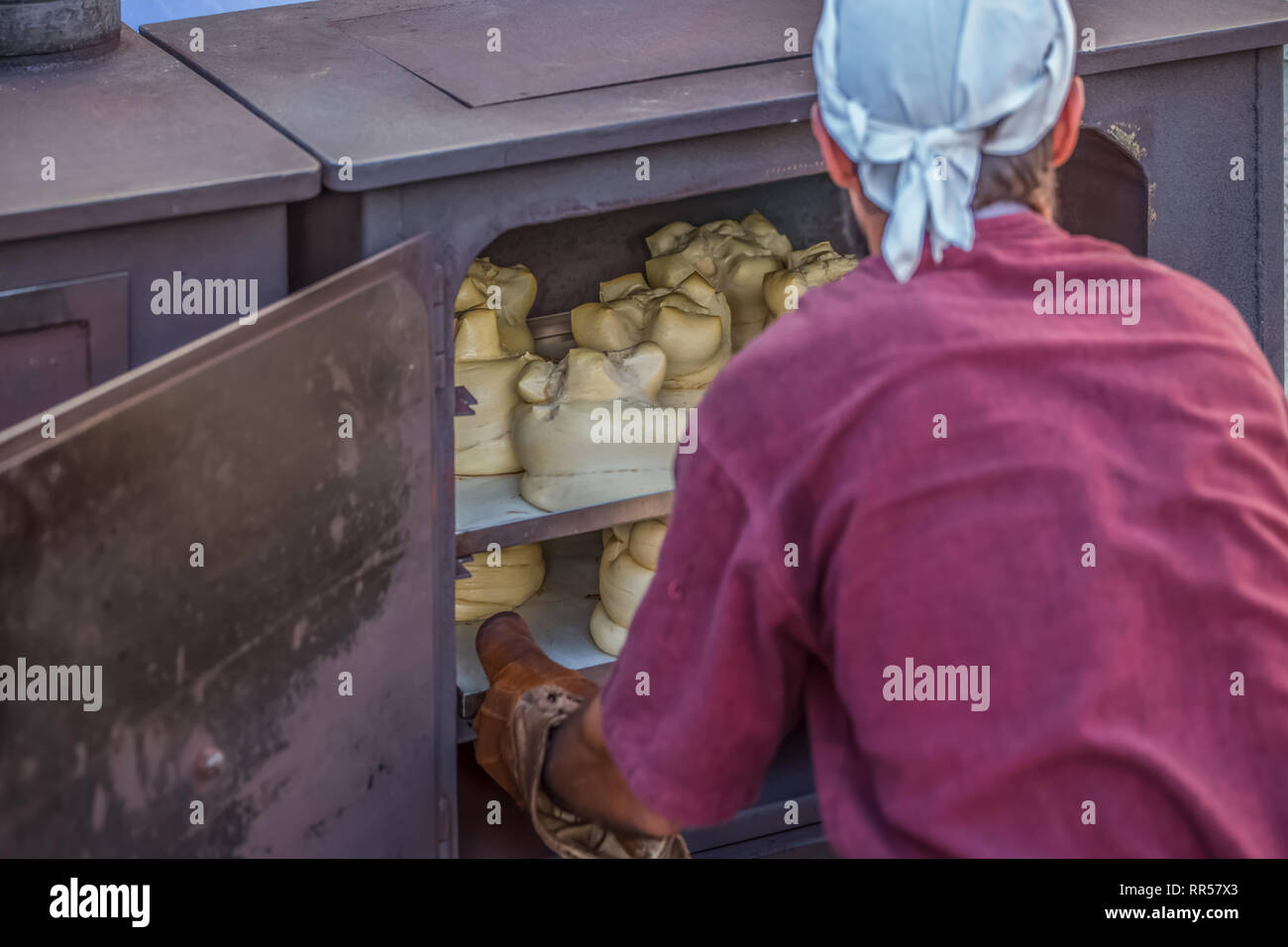 Traditional metal oven view with baker removing the already cooked bread... Stock Photo