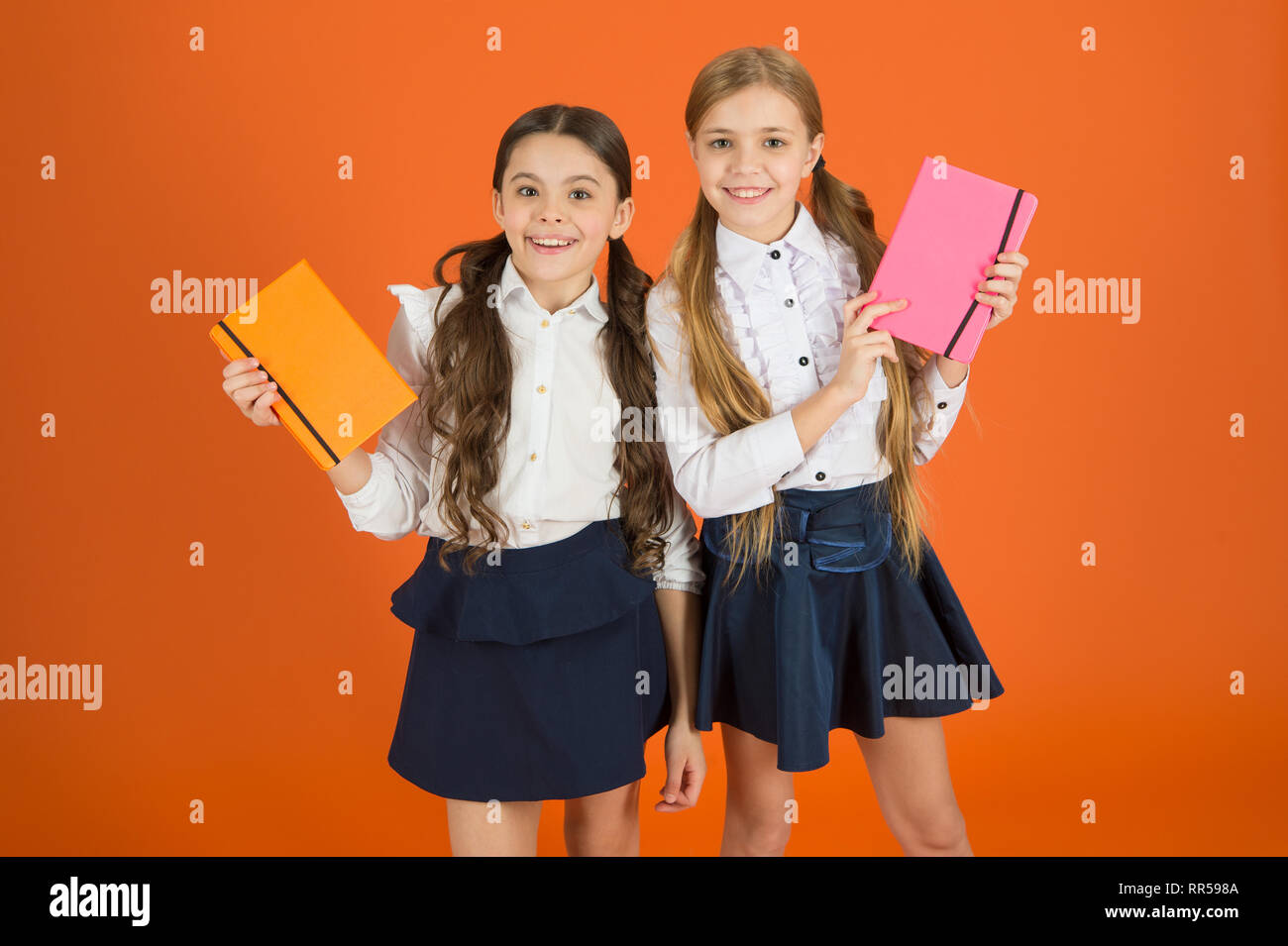 Smart and adorable. Cute schoolgirls holding lesson books. Little children with school diaries for making notes. School children learn reading books. Small girls classmates with workbooks for writing. Stock Photo