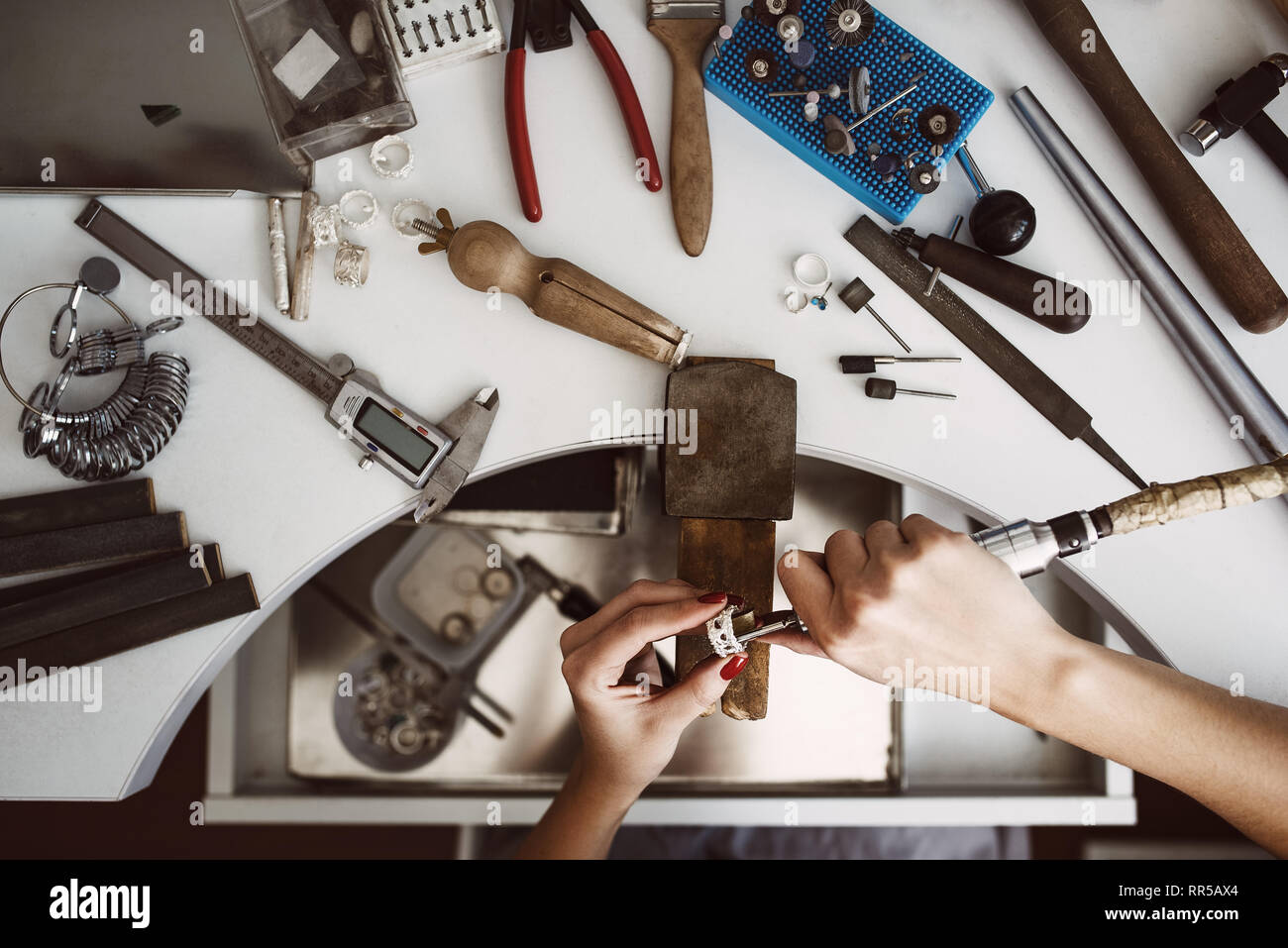 Creative chaos. Top view of jeweler's workbench with different tools for making jewelry. Female jeweler's hands polishing a silver ring with grinding  Stock Photo