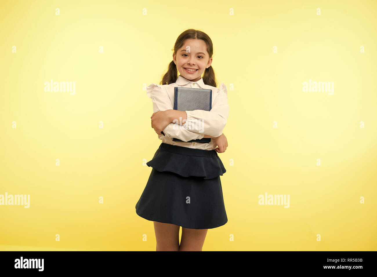 Happy girl hold book on yellow background. Little schoolgirl smile with textbook. Fashion bookworm. First school day. Learning is my game. Stock Photo