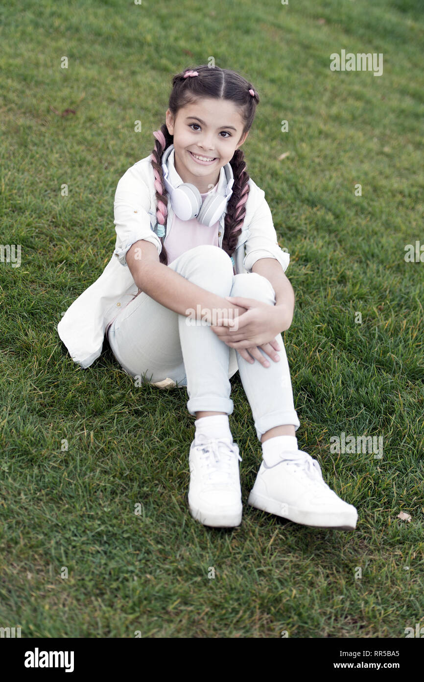 Secrets to raising happy child. Girl cute kid green grass background. Healthy emotional happy kid relaxing outdoors. Get happy yourself. Girl braids hairstyle and modern headphones enjoy relax. - Stock Image