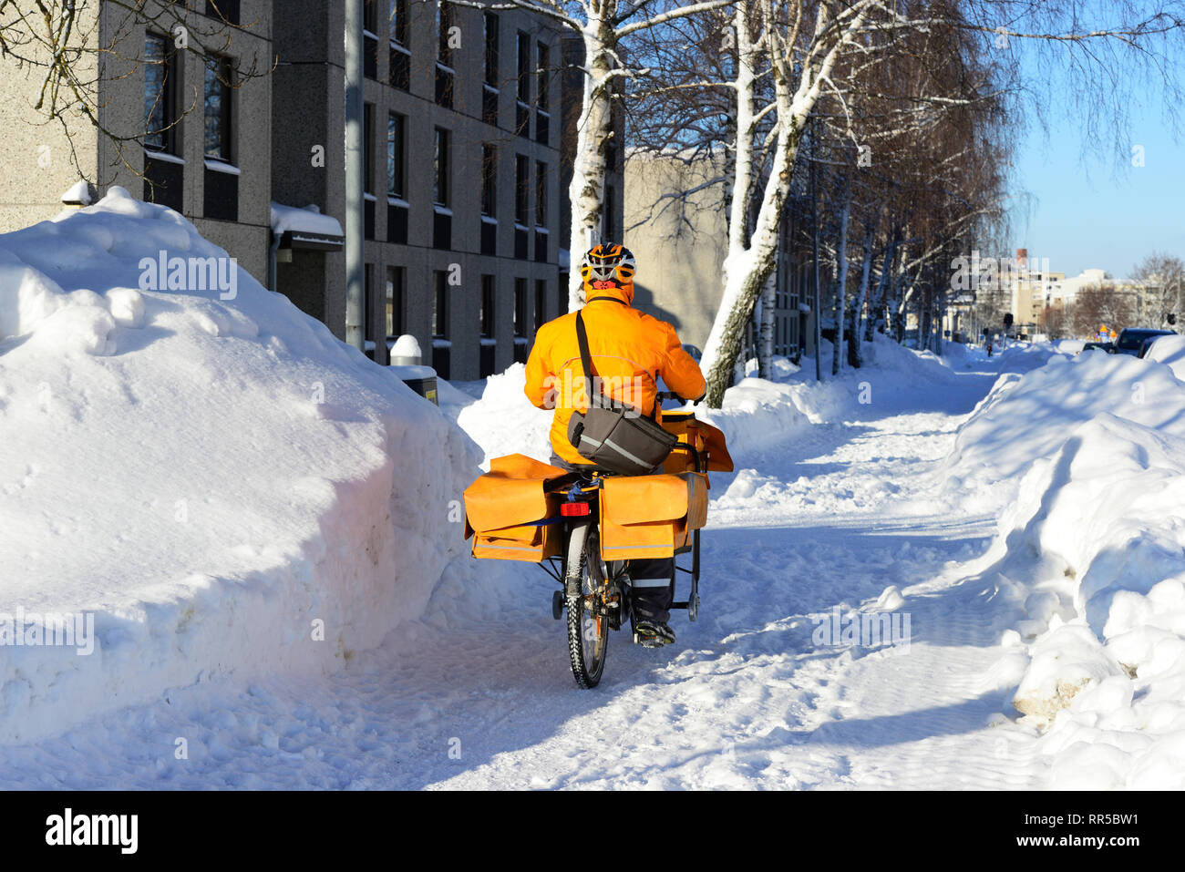 the postman rides a bicycle among the snowdrifts in Finland - Stock Image