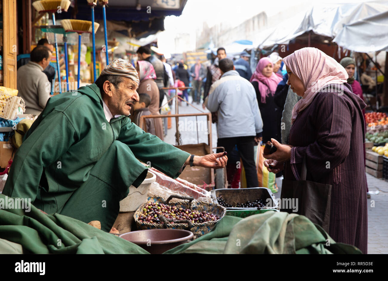 Olive vendor and customer in the souq of the Fes medina - Stock Image