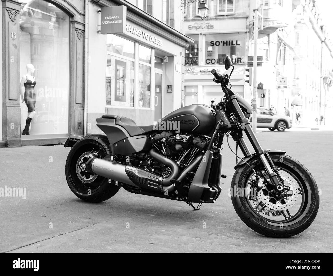 Strasbourg, France - Feb 16, 2018: Parked in the city brand new Harley Davidson bike motorbike with shops and buildings in the background black and white - Stock Image