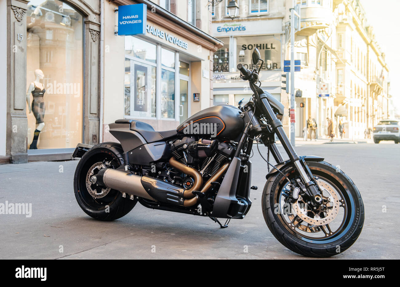 Strasbourg, France - Feb 16, 2018: Parked in the city brand new Harley Davidson bike motorbike with shops and buildings in the background - Stock Image