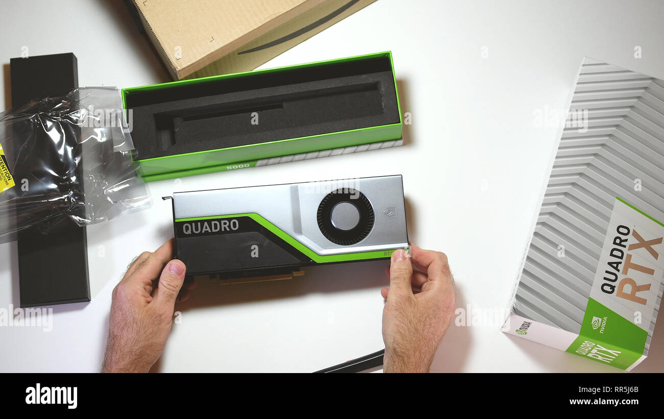 Paris, France - Feb 20, 2019: View from above POV man unboxing latest Nvidia Quadro RTX 5000 workstation professional video card GPU for CAD holding the card and accesories - Stock Image