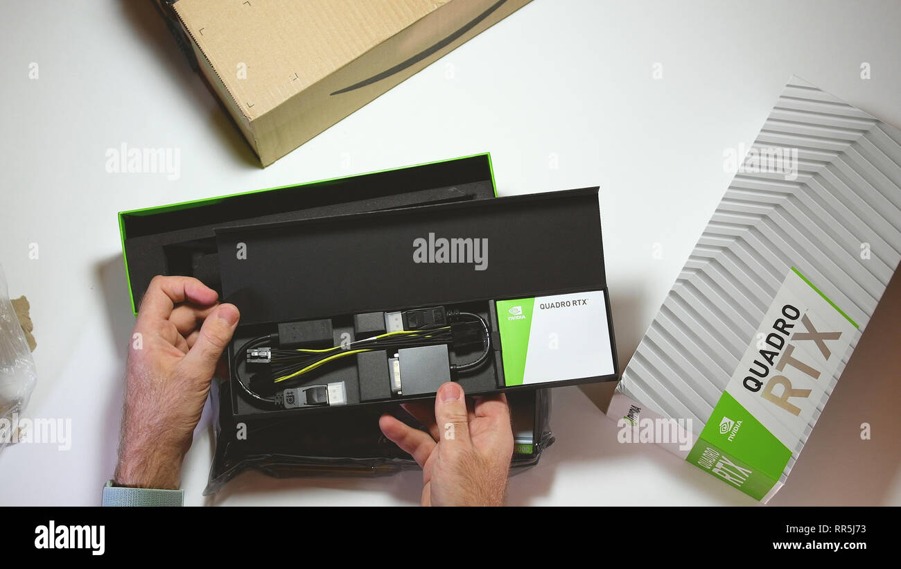 Paris, France - Feb 20, 2019: View from above POV man unboxing latest Nvidia Quadro RTX 5000 workstation professional video card GPU for CAD CGI cavbles accessories and connectors - Stock Image