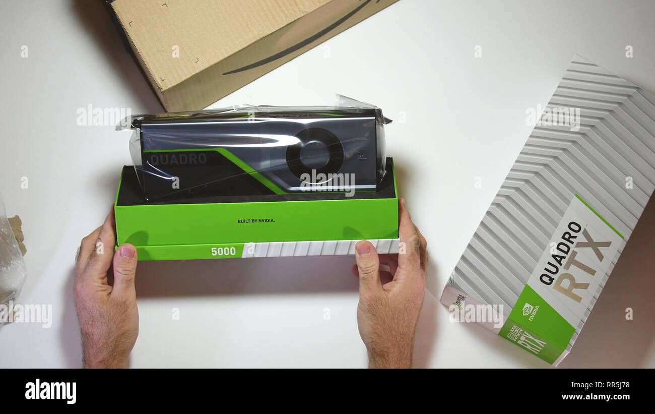 Paris, France - Feb 20, 2019: View from above POV man unboxing latest Nvidia Quadro RTX 5000 workstation professional video card GPU for CAD CGI scientific calculations and machine learning looking at contents - Stock Image