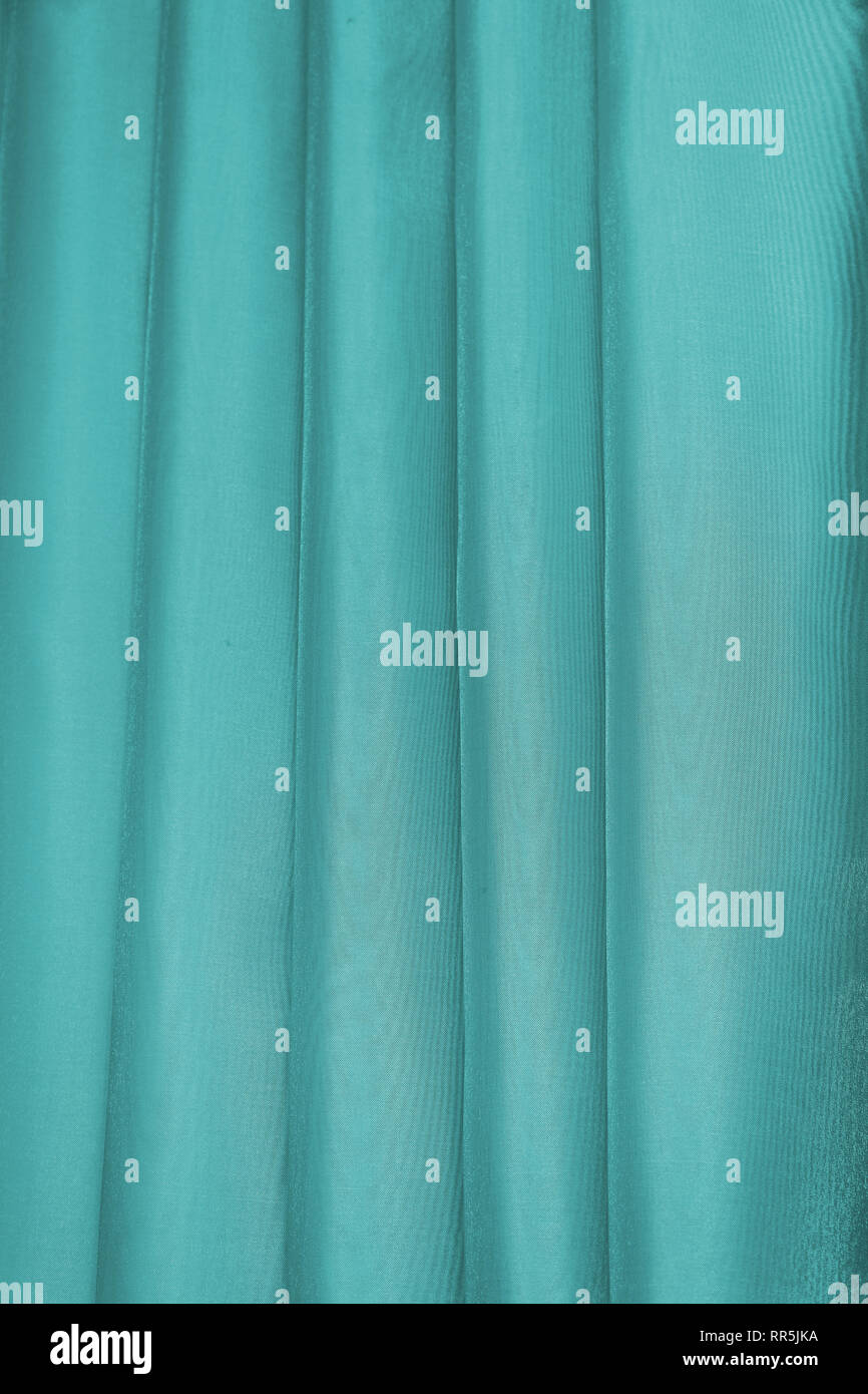 Vertical folds on green organza curtains - Stock Image
