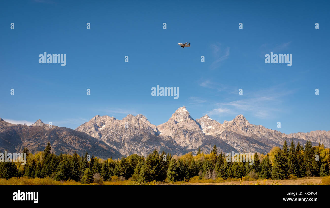 Teton mountain range with a commercial airlines flying over them - Stock Image