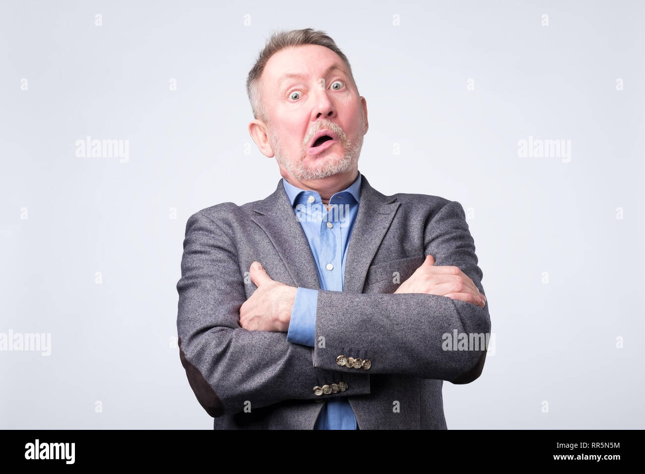 Senior man in suit is puzzled and confused musing about business problems. - Stock Image