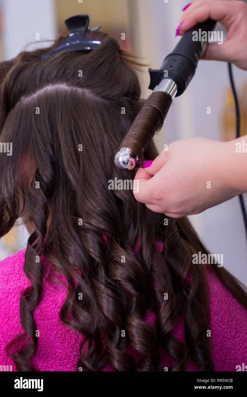 The hairdresser curl hair with figaro in the salon. - Stock Image