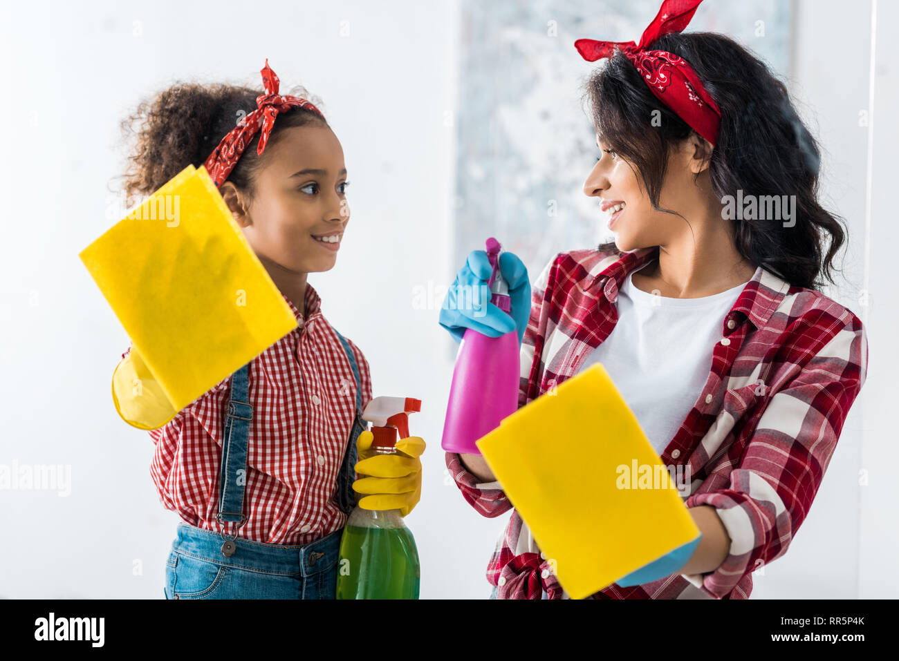 smiling african american mom and daughter with yellow rags and spray bottles cleaning house - Stock Image