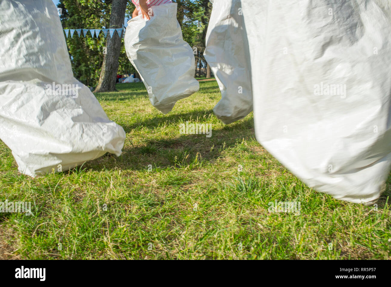 Children having a sack race in the park. Classic games concept. Motion blurred - Stock Image