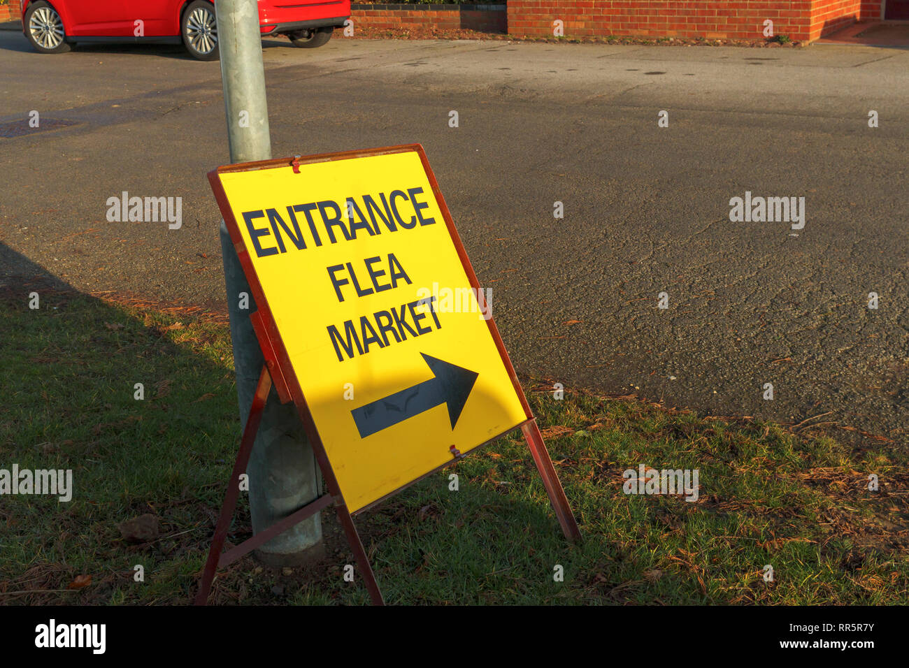 Yellow temporary entrance sign with direction arrow to a flea market event in a hall in Lincolnshire Showground, Lincoln, Lincolnshire, UK - Stock Image