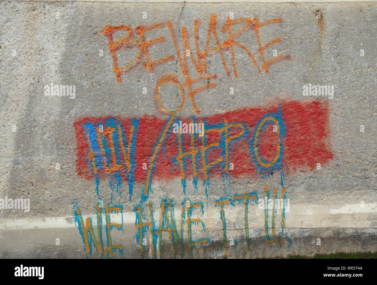 HIV and Hep C graffiti painted on building wall - Stock Image